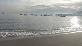 De golven van het warme overzees lopen vroeg op het zandige strand in de ochtend, Pemuteran Bali stock footage
