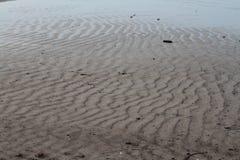 De golven van het zand op het strand stock fotografie