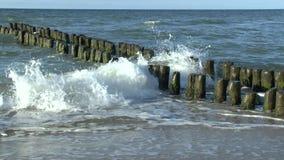 De golven van de Oostzee breken op een oude houten golfbreker stock video