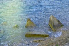 De golven van de overzeese afstraffing op de reusachtige keien op de kust royalty-vrije stock fotografie