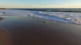 De golven wassen zacht omhoog op het strand stock video