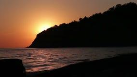 De golven wasten zacht op het strand, en gaan dan achteruit wanneer de zon begint te vallen stock video