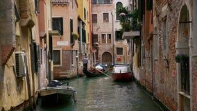 De gondel die van Venetië tussen boten op het kanaal overgaan stock video