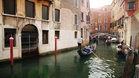 De gondel drijft langs een smal kanaal tussen de typische gebouwen van Venetië stock video
