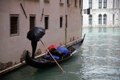 De gondel met twee toeristen drijft op een kanaal in Venetië, Italië stock fotografie