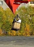 De gondel van een ballon met drie aëronauten komt van de grond en begint toe te nemen Royalty-vrije Stock Afbeelding