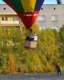 De gondel van een ballon met drie aëronauten komt van de grond en begint toe te nemen Stock Foto's