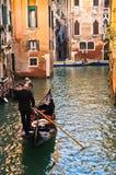De gondelier drijft een gondel bij smal kanaal in Venetië Stock Fotografie