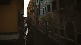 De gondels die door een smal kanaal in Venetië in de avond drijven stock footage