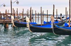 De gondels legden op houten dok vast door het Tekenvierkant van Heilige met de kerk van San Giorgio Maggiore en eiland met bewolk royalty-vrije stock afbeelding