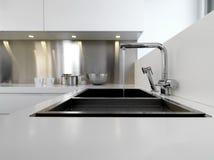 De gootsteen en de kraan van het staal in de moderne keuken Stock Foto
