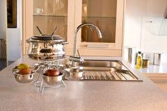 De gootsteen van de keuken met de kraan en Werktuigen voor fondu Stock Afbeeldingen