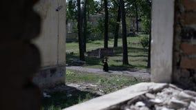 De gotische kandelaar van de meisjeholding en het lopen op herenhuissteeg tussen bomen en geruïneerde gebouwen stock videobeelden