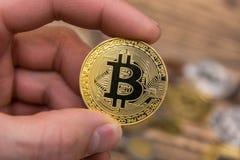 De gouden Bitcoin-holding bemant binnen vingersclose-up Stock Foto