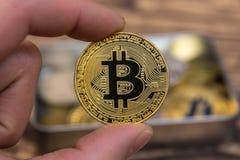 De gouden Bitcoin-holding bemant binnen vingersclose-up Royalty-vrije Stock Foto's
