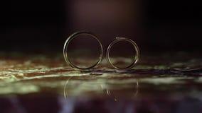 De gouden bruiloftringen op marmer ontwikkelt van de kaderbeweging stock videobeelden