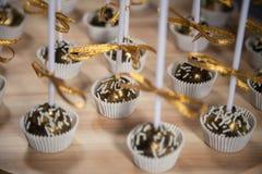 De gouden cake knalt op houten tribune Stock Afbeeldingen
