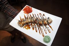 De gouden draaksushi rolt met tonijn, paling, komkommer, sesamzaden op een witte plaat met wasabi en imbrem stock foto