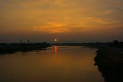 De gouden gele hemel met de zon plaatst op de horizon Stock Afbeeldingen