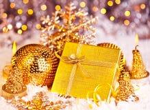 De gouden gift van Kerstmis met snuisterijen en kaarsen Royalty-vrije Stock Foto's