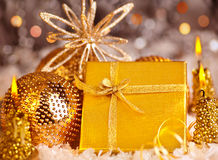 De gouden gift van Kerstmis met snuisterijen en kaarsen Stock Foto