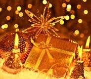 De gouden gift van Kerstmis met snuisterijendecoratie Stock Fotografie