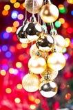 De gouden hangende snuisterijen van Kerstmis met lichten bij rug Stock Afbeeldingen