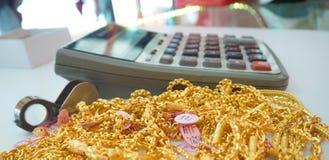 De gouden juwelen op het bureau met grote calculator Royalty-vrije Stock Afbeelding