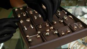 De gouden juwelen voor vrouwen, die voor verkoop in een juwelenopslag worden blootgesteld, Juwelier zetten gouden juwelen op de t stock footage