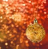 De gouden Kerstmisbal op defocused achtergrond Royalty-vrije Stock Foto's