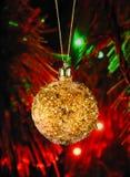 De gouden Kerstmisbal op defocused achtergrond Stock Fotografie