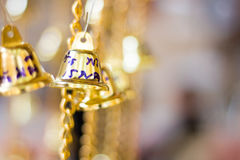 De gouden Kerstmisklokken die als nieuw jaarspeelgoed hangen defocused achtergrond Stock Foto's