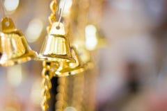 De gouden Kerstmisklokken die als nieuw jaarspeelgoed hangen defocused achtergrond Stock Afbeelding