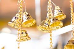 De gouden Kerstmisklokken die als nieuw jaarspeelgoed hangen defocused achtergrond Stock Fotografie