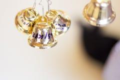 De gouden Kerstmisklokken die als nieuw jaarspeelgoed hangen defocused achtergrond Royalty-vrije Stock Foto's