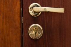 De gouden kleur van het deurhandvat met een slot stock afbeeldingen