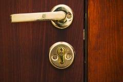 De gouden kleur van het deurhandvat met een slot stock afbeelding
