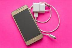 De Gouden kleur van Smartphone en witte USB-lader op roze achtergrond stock afbeelding