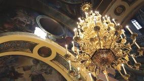 De gouden kroonluchter met imitatiekaarsen hangt van plafond van tempel stock videobeelden