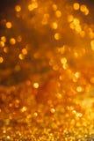 De gouden lichte bokehtextuur of schittert lichten feestelijke gouden backgrou Royalty-vrije Stock Foto's
