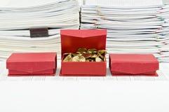 De gouden muntstukken in open rood vakje schikken voor financiënrekening Stock Foto's