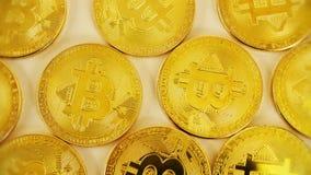 De gouden muntstukken van bitcoins liggen chaotically op de lijst Blockchain is de technologie van de toekomst Close-up stock videobeelden