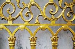 De gouden oude vervaardigde achtergrond van het omheiningsclose-up Gesmede overladen mooie patroon gouden poort stock foto's
