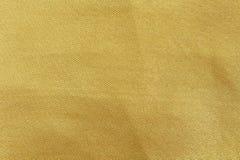 De gouden samenvatting van de stoffentextuur voor achtergrond royalty-vrije stock foto's