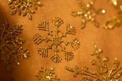De gouden sneeuwvlok schittert patroon op bruin royalty-vrije stock afbeelding