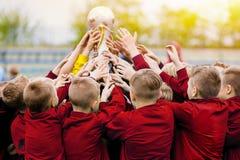 De gouden Trofee heft op De Trofee van Team Raising Golden Winning Football van het kinderenvoetbal royalty-vrije stock afbeelding