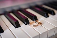 De gouden trouwringen liggen op de pianosleutels stock foto