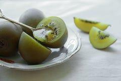 De gouden uitstekende plaat van Kiwifruit Stock Foto's