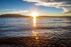 De gouden zonsterren denken van de oppervlakte van glazig water na terwijl de zon achter vlakke bergen in de afstand plaatst royalty-vrije stock afbeeldingen