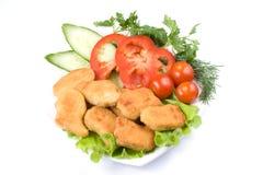 De goudklompjes van de kip met groenten Stock Foto